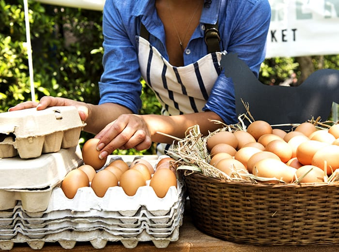 eggs in baskets and crates set out on table, most are brown eggs with some white eggs. A woman hovers above the eggs as she places them into the crates and baskets. She is wearing a long sleeve blue shite with a a blue striped apron.